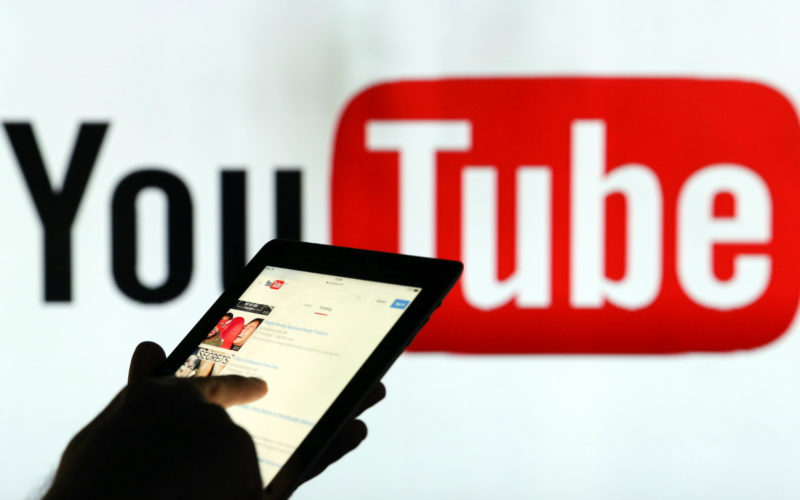 A man is seen as a silhouette as he checks a mobile device whilst standing against an illuminated wall bearing YouTube Inc.s logo in this arranged photograph in London, U.K., on Tuesday, Jan. 5, 2016. YouTube Inc. provides consumer media and entertainment through its website. Photographer: Chris Ratcliffe/Bloomberg